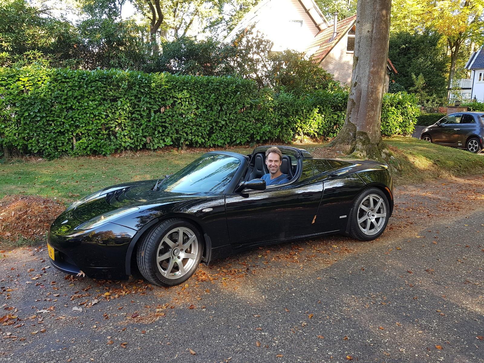 Mark in een zwarte Tesla Roadster