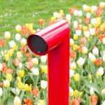 rode design-laadpaal met op de achtergrond tulpen in wit geel en oranje